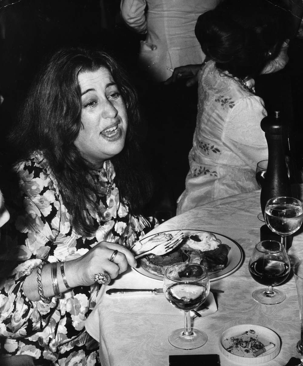 American musician Mama Cass Elliot (1941 - 1974) formerly of the Los Angeles folk-pop harmony group The Mamas And The Papas eats at a party at Crockford's casino in London, circa 1974. (Photo by Joe Bangay/Evening Standard/Getty Images)