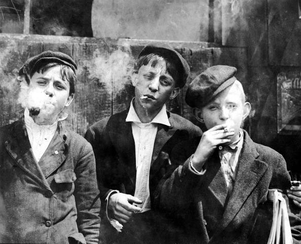 Portrait of three newsboys smoking outside Skeeter's Branch, at Jefferson near Franklin Avenue at 11 in the morning, St. Louis, MO, May 9, 1910.