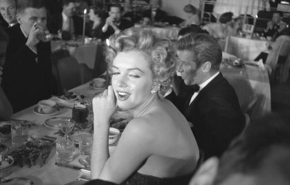 American actress Marilyn Monroe (1926 - 1962) covers her mouth as she sits at a table at the Foreign Press Association of Hollywood's First Annual International Film Festival, at the Club Del Mar, Santa Monica, California, January 26, 1952. Fellow actor Richard Basehart (1914 - 1984) sits to her right. Monroe won a 'Henrietta' award, her first of several over the years