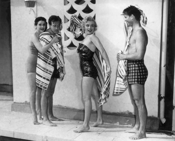 1950: American actor Marilyn Monroe (1926-1962) in a bathing suit rubs off with a towel, as a man and another couple watch.