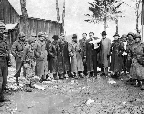 After their surrender, a group of German rocket scientists pose with members of the US 7th Army, 44th Infantry Division, near Oberammergau, Germany, May 2, 1945. Among those pictured are Dieter Huzel (1912 - 1994) (left center, in leather longcoat and hat) and, continuning left,  Magnus von Braun (1919 - 2003) (left, in leather longcoat and no hat), Major General Walter Dornberger (1895 - 1980), Lieutenant Colonel Herbert Axster (1899 - 1991), Wernher Von Braun (1912 - 1977) (arm in cast), Hans Lindenberg (1904 - ?), and Bernhard Tessmann (1912 - 1998).
