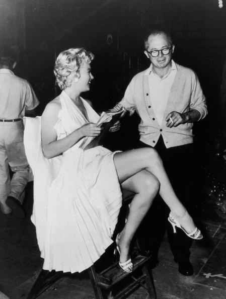 1955: American actor Marilyn Monroe (1926 - 1962) holds a script while sitting next to Austrian-born director Billy Wilder (1906 - 2002) on the set of his film, 'The Seven Year Itch'. Monroe is wearing a white halter dress with a pleated skirt