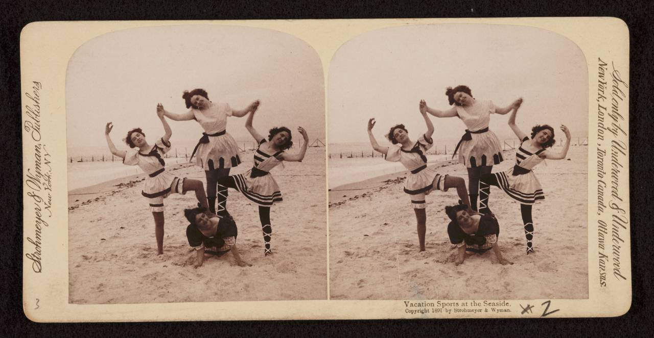 Stereograph shows women in bathing suits striking poses on the beach at Coney Island.