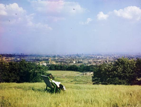 A figure sits in a deckchair on Parliament Hill, Hampstead Heath, overlooking ruins from the Battle of Britain, World War II, London, United Kingdom, circa 1940. At the bottom of the hill is the Athletics Track, and a number of allotments.