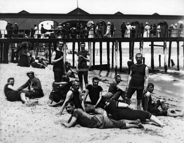 A large group of male bathers by a boardwalk at the ocean, United States circa 1885.
