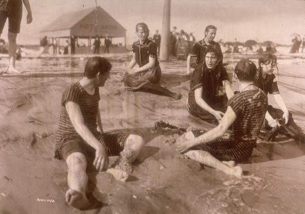 1897:  Young men and women wearing bathing suits sit in wet sand at the water's edge, Far Rockaway Beach, New York City.