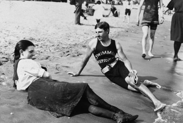 1898:  Portrait of a bathing suit-clad woman and a swimming instructor lying close to the surf on Midland Beach, Staten Island, New York.