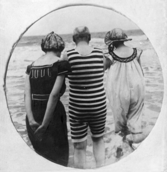 circa 1905:  Three bathers walk into the sea for a paddle. A circular image in a square setting.  (Photo by Hulton Archive/Getty Images)