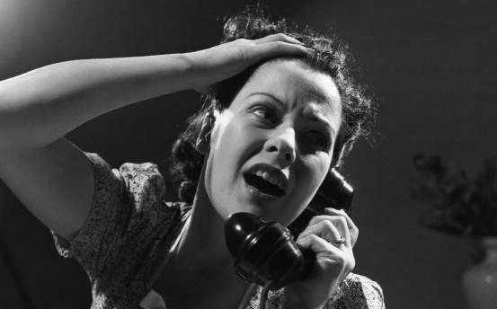24th June 1940:  An exasperated woman cries for help on the phone.  (Photo by Fox Photos/Getty Images)