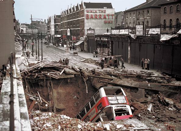 A number 88 bus lies in a large crater in the road in Balham, London, the morning after a German air raid during the Battle of Britain, 15th October 1940.