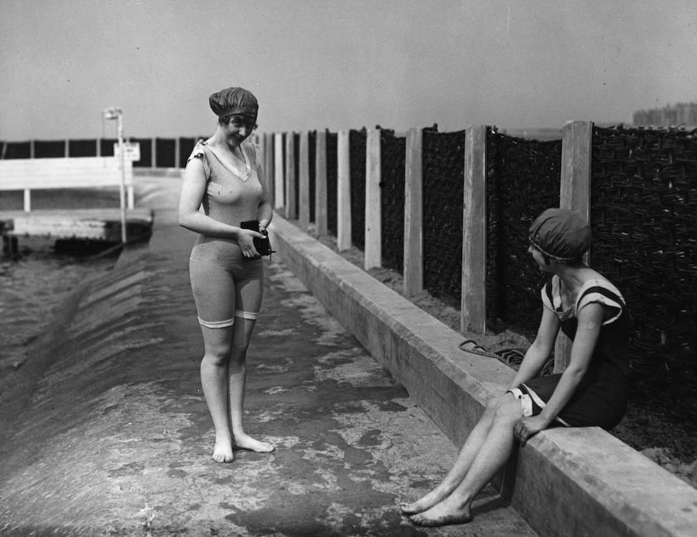 Two women in swimwear amuse themselves by taking photographs.   (Photo by Topical Press Agency/Getty Images)