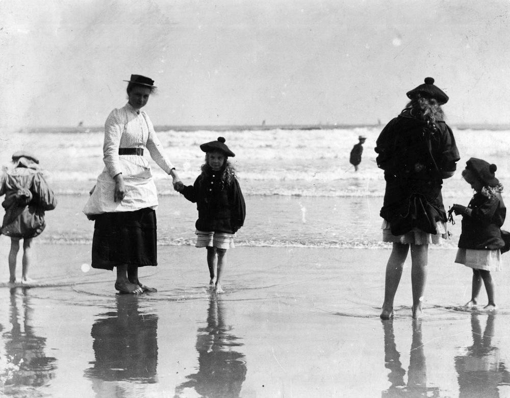 Girls wearing tam o'shanters paddling at the seaside.   (Photo by Paul Martin/Getty Images)