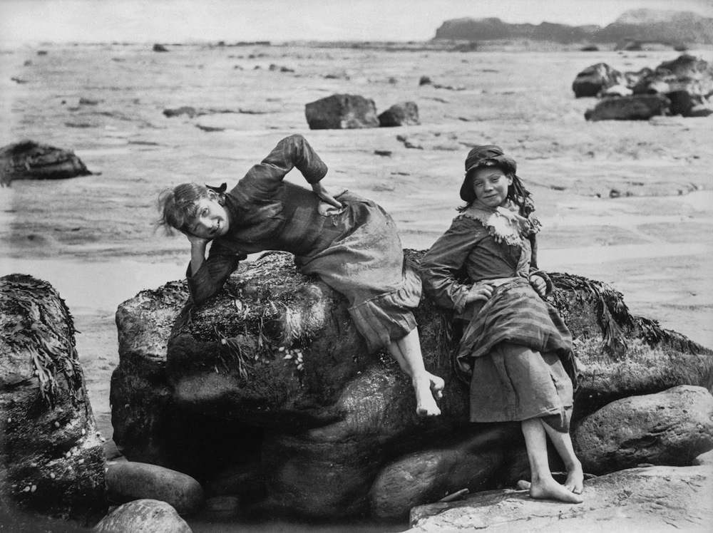 Two girls on the rocks by the sea.   (Photo by Frank Meadow Sutcliffe/Getty Images)