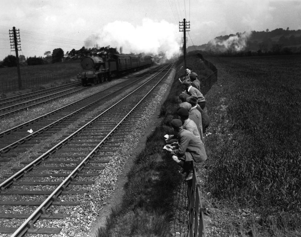 May 1933:  Trainspotting schoolboys watching an LMS train pass by at Tring.  (Photo by Fox Photos/Getty Images)
