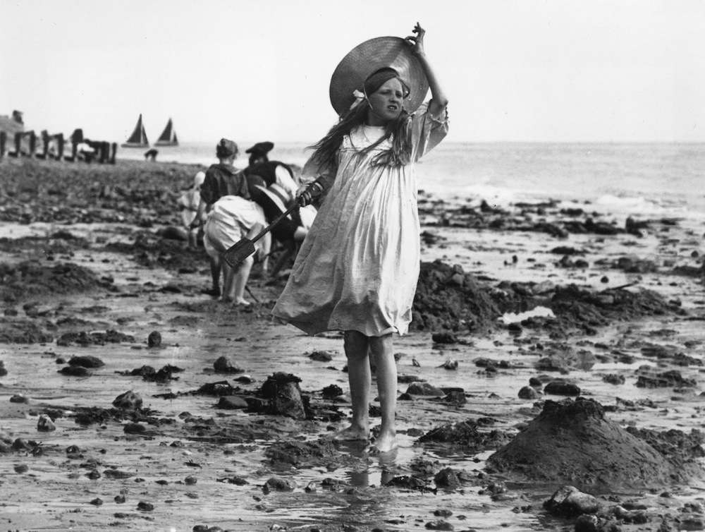 circa 1895:  A young girl taking a break from making sandcastles on the beach.  (Photo by F J Mortimer/Getty Images)