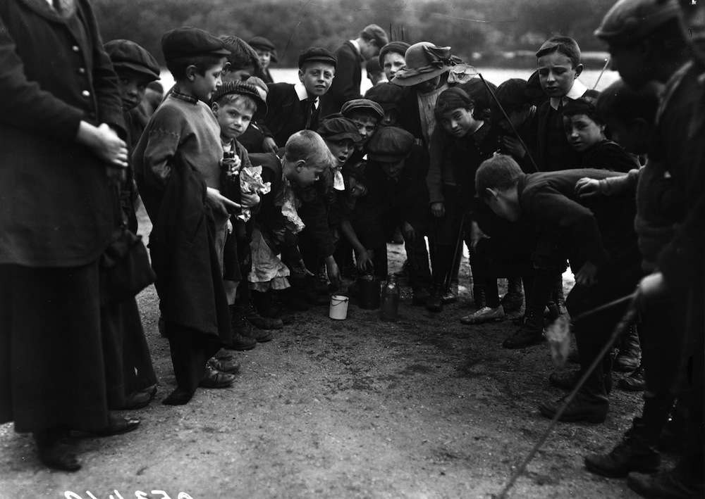 circa 1905:  London school children fishing during the holidays; the envy of the crowd has caught a gudgeon.  (Photo by Topical Press Agency/Getty Images)