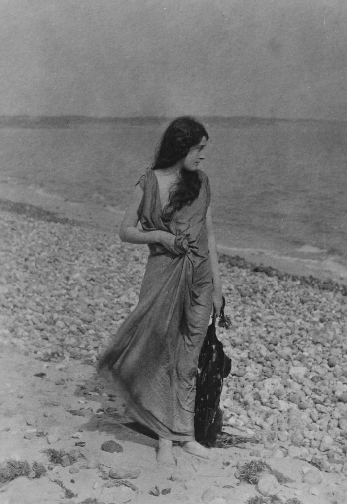 circa 1899:  A windswept woman strolls along a pebble beach.  (Photo by Hulton Archive/Getty Images)