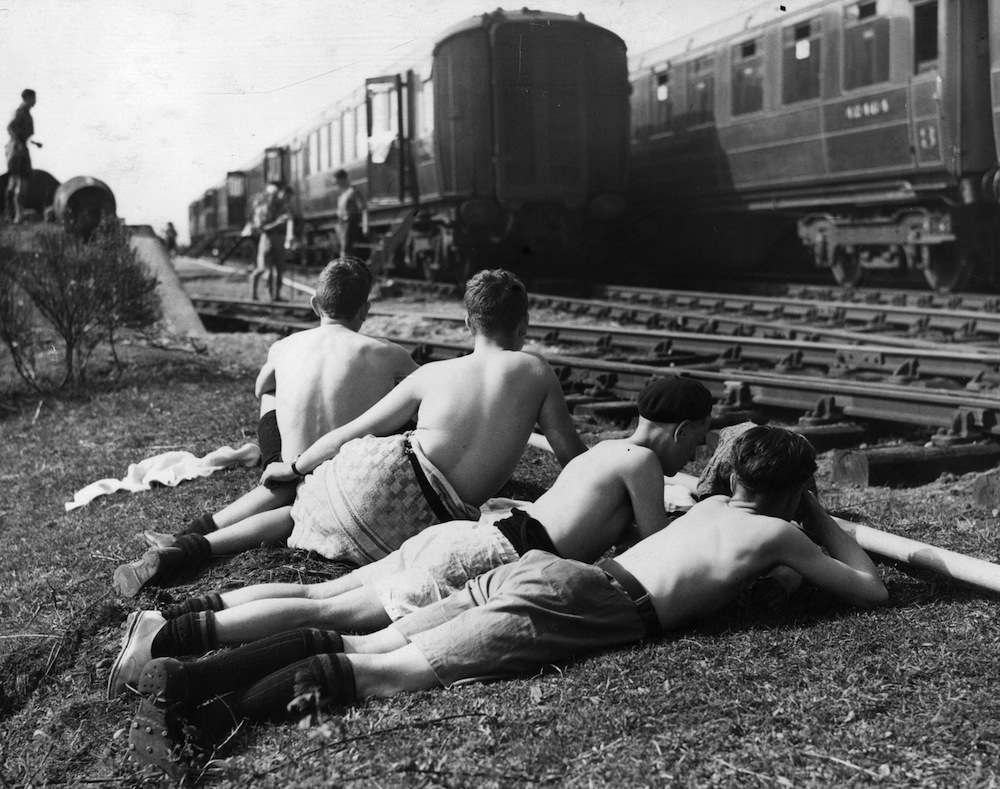circa 1935:  A group of boys relax in the sun near a railway track.  (Photo by Fox Photos/Getty Images)