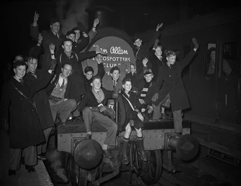 January 05, 1953: A group of young trainspotters on board a special train at London Bridge Station, London, 5th January 1953. The 'Spotters' Special' is taking four hundred young rail enthusiasts on a trip to the locomotive works and engine sheds at Stratford in East London. The trip has been organized by the Ian Allen Loco Spotters' Club, which is celebrating its tenth anniversary and the enrolment of its one hundred-thousandth member. (Photo by Harry Todd/Fox Photos/Hulton Archive/Getty Images)