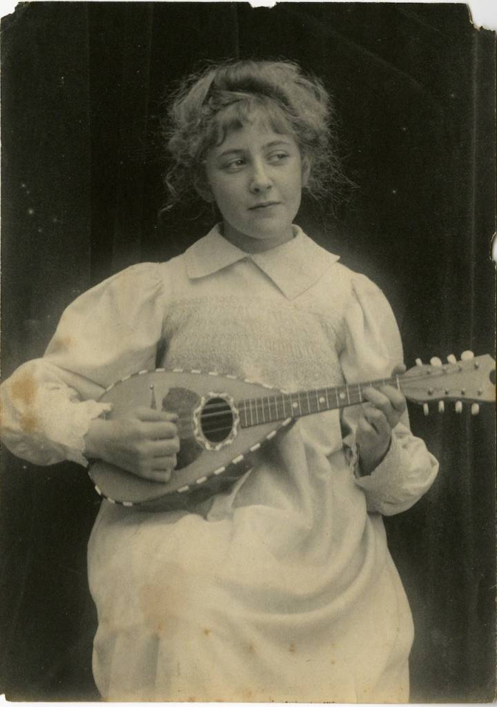 Agatha playing a mandolin. c 1898. 'I am today the same person as that solemn little girl with pale flaxen sausage-curls. The house in which the spirit dwells, grows, develops instincts and tastes and emotions and intellectual capacities, but I myself, the true Agatha am the same.'