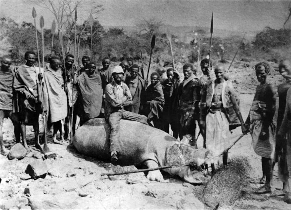 The Italian explorer Vittorio Bottego, surrounded by local people armed with spears, posing seated on a hippopotamus killed along the banks of the Juba. Ethiopia, 1890s