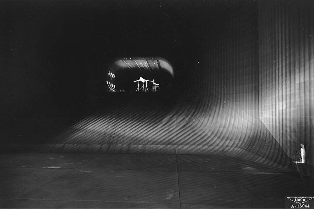 "(1947) Looking down the throat of the world's largest tunnel. The scene is NACA's 40 x 80 foot wind tunnel at Ames Aeronautical Laboratory, Moffett Field, California, which when it was built was the world's largest. The camera is stationed in the tunnel's largest section, 173 feet wide by 132 feet high. Here at top speed the air, driven by six 40 foot fans, is moving about 35 to 40 miles per hour. The rapid contraction of the throat (or nozzle) speeds up this air flow to more than 250 miles per hour in the oval test section, which is 80 feet wide and 40 feet high. The tunnel encloses 900 tons of air, 40 tons of which rush through the throat per second at maximum speed. Dwarfed by the immensity of the tunnel structure, the experimental model seen here is actually almost 50 feet long. Embodying a sharply swept-back wing suitable for supersonic flight, it is undergoing tests designed to improve the landing characteristics of this type of airfoil. Mounted on struts connected to scales under the test section, it is ""flown standing still"" while each element such as lift and drag is measured and air pressures occurring across the wing are recorded. Information gathered from such tests were made available to the nation's aircraft manufacturers by the NACA (now NASA), an independent agency of the U.S. Government."