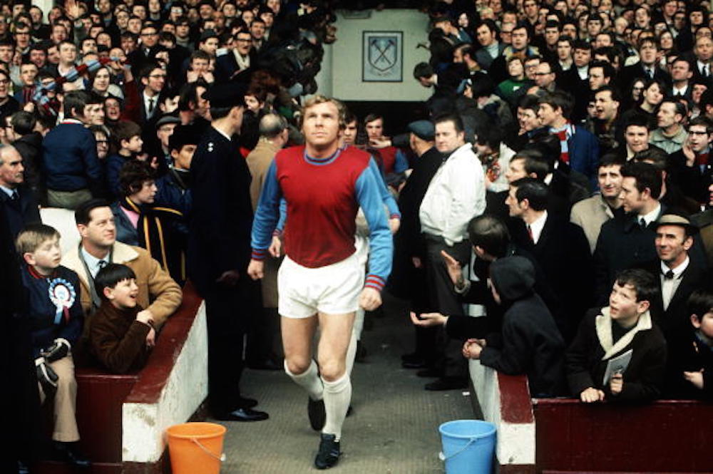 Football, London, 1970, West Ham captain Bobby Moore leads out his team before a game at Upton Park as the crowd watches  (Photo by Rolls Press/Popperfoto/Getty Images)