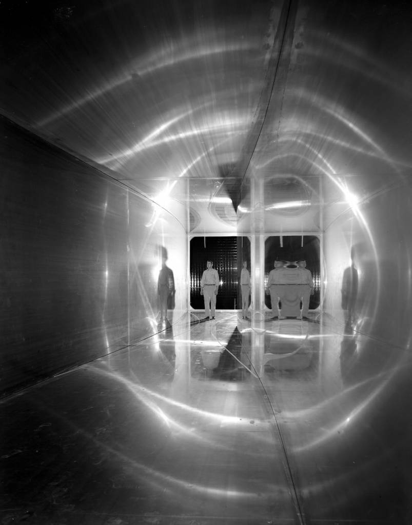 Abe Silverstein Supersonic Wind Tunnel  (C-1956-42059): This nozzle interior view shows the right sidewall distinctly curved and the left wall almost flat. Note the man's shadow and multiple reflections in the polished walls.