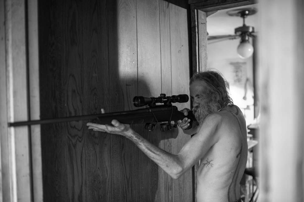 Carl, an Imperial Wizard of a southern-based Ku Klux Klan realm, takes aim with a pellet gun at a large cockroach