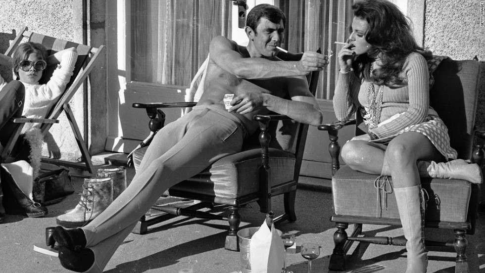 George Lazenby offers Helena Ronee a light during a break from filming.