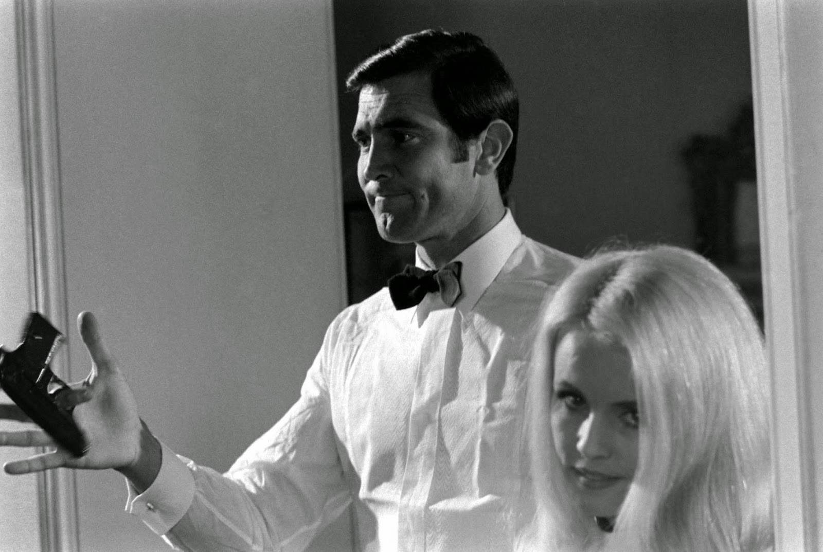 George Lazenby twirls a gun beside potential Bond Girl Marie-France Boyer, 1967.