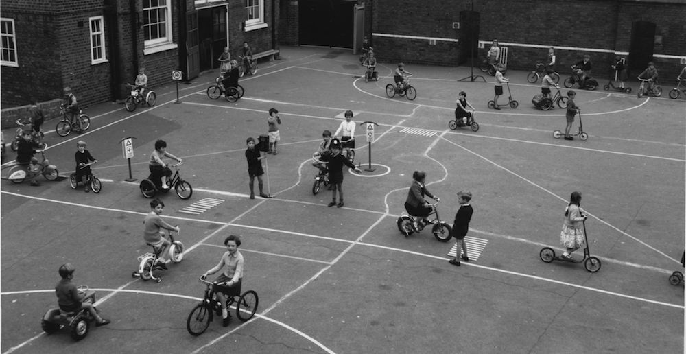 2nd November 1962: Schoolchildren at the Queen's Park Primary School on Droop Street, London, learn about Safety First and the Highway Code. They are using bicycles and scooters on a playground marked out with roadways, zebra crossings, junctions with traffic lights, and various road signs. (Photo by Fred Morley/Getty Images)