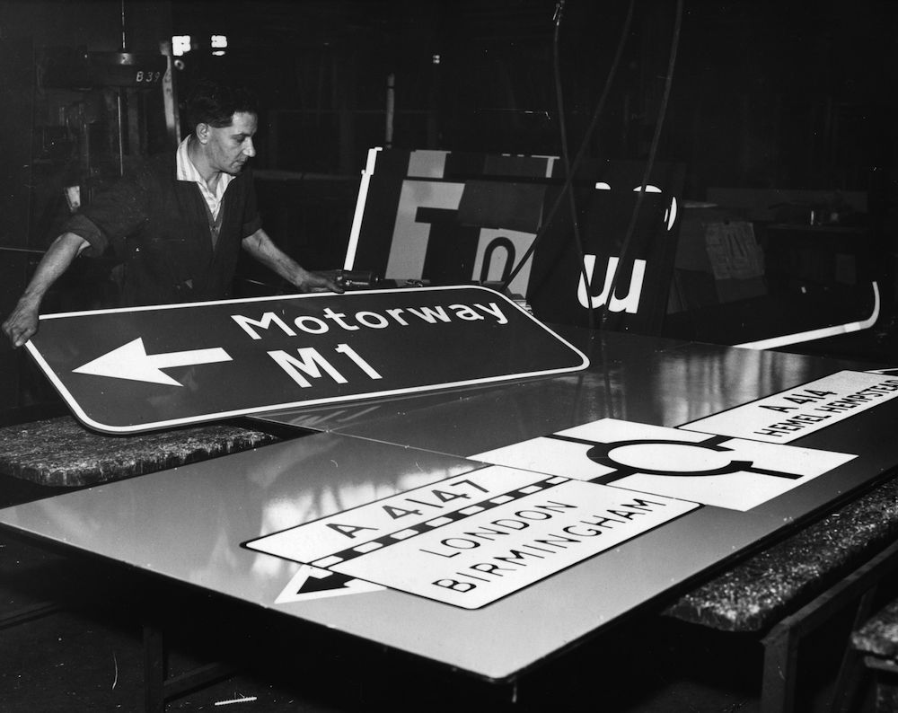 30th October 1959: A worker at 'Franco Signs' in Boreham Wood, Hertfordshire prepares new motorway signs for the stretch of road between London and Birmingham. (Photo by William Vanderson/Fox Photos/Getty Images)