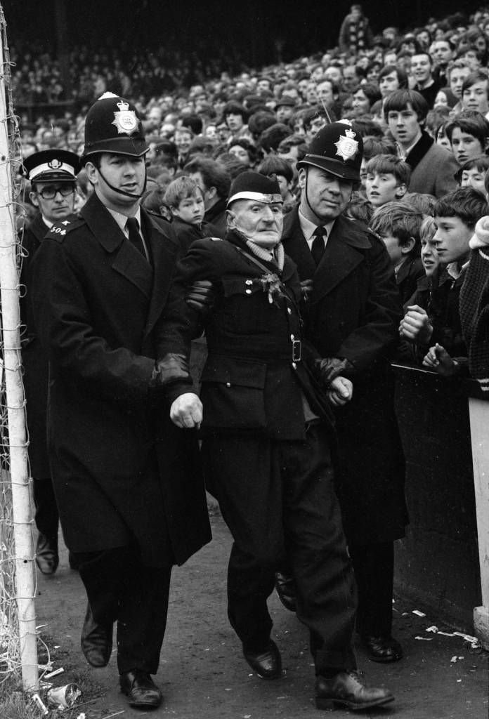 3rd April 1971:  A veteran West Ham supporter being led away from the terraces by police during the match against Manchester United at Upton Park.  (Photo by Leonard Burt/Central Press/Getty Images)