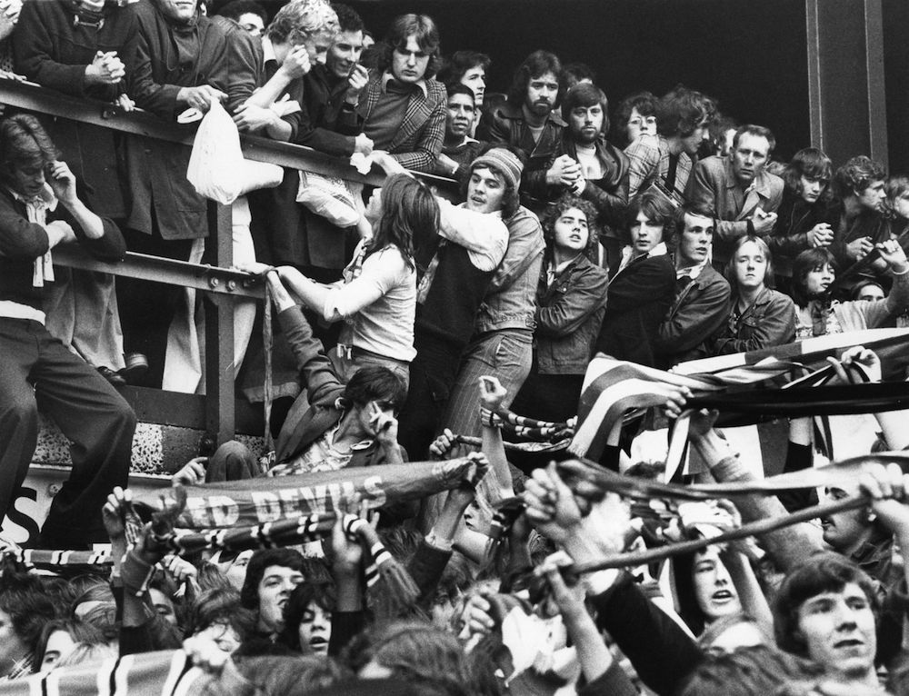 25th October 1976:  Rowdy Manchester United football fans take to the stands as they sense the oncoming defeat of their team by West Ham at the Upton Park football ground in London.  (Photo by Roger Jackson/Central Press/Getty Images)