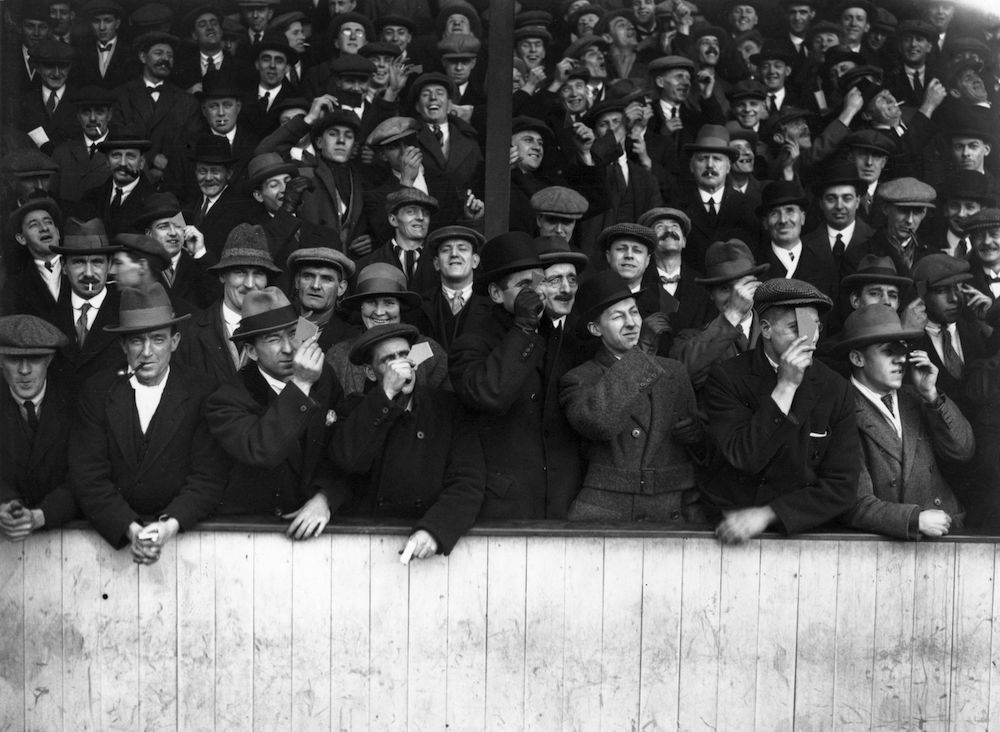 4th April 1936:  Spectators at Upton Park to see the football match between West Ham United and Aston Villa take a moment to view the eclipse of the sun during play.  (Photo by Topical Press Agency/Getty Images)