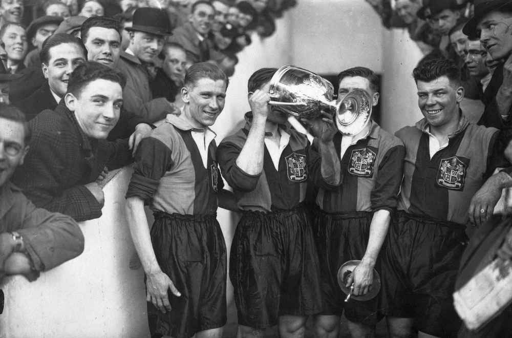 3rd April 1937:  Robbins, captain of Dulwich Hamlet amateur football team, drinks in celebration from the trophy, after his side's Amateur Cup final win over Leyton at Upton Park.  (Photo by J. A. Hampton/Topical Press Agency/Getty Images)