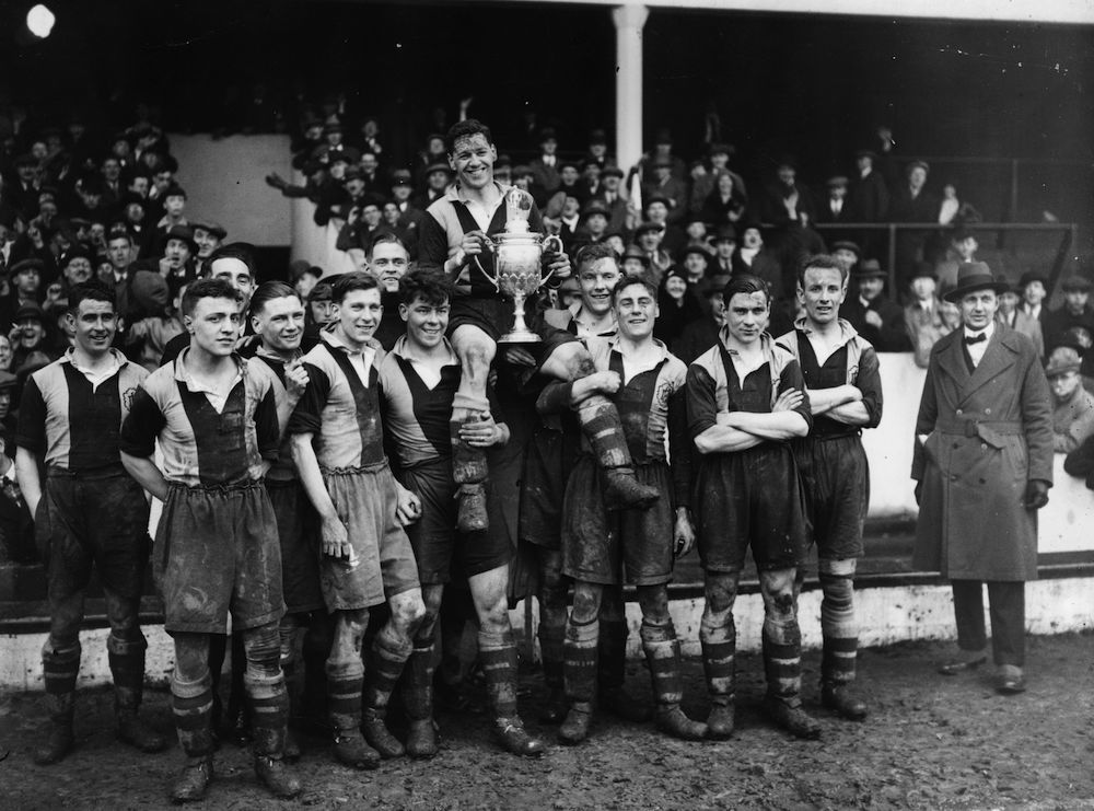 16th April 1932:  The players of Dulwich Hamlet amateur football club hold their captain and the trophy aloft after their victory over Marine (Liverpool) in the Amateur Cup final at Upton Park.  (Photo by H. F. Davis/Topical Press Agency/Getty Images)