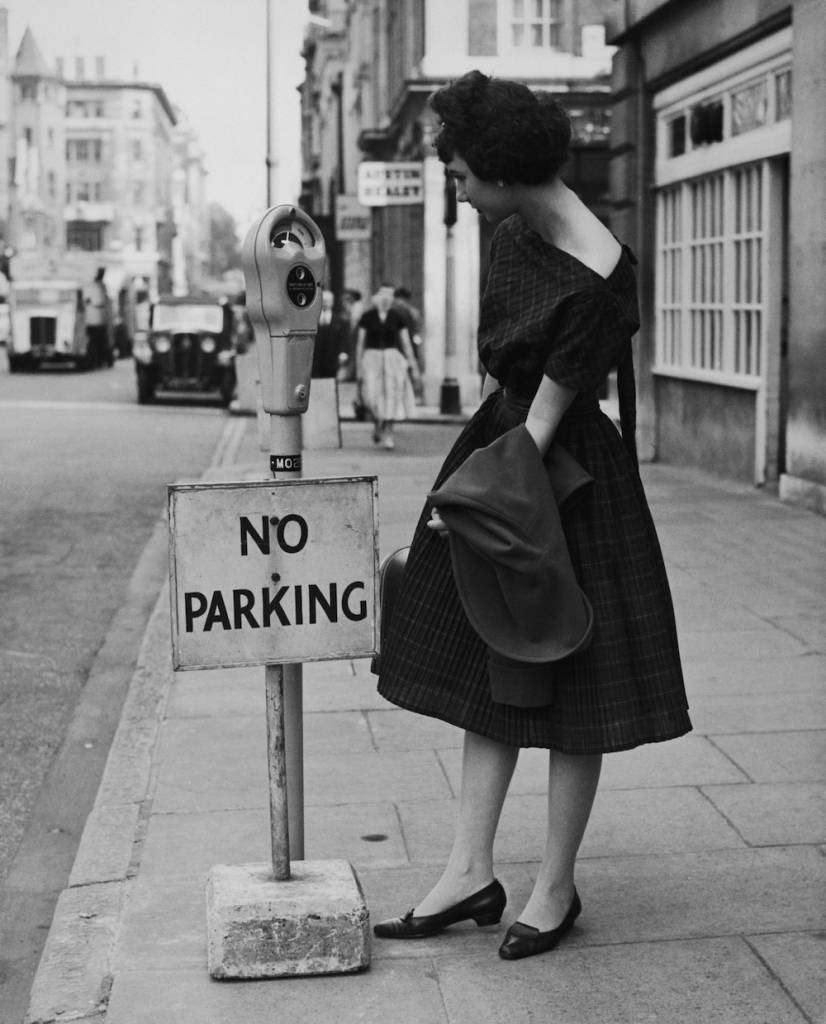 Yvonne Brecher examining a newly-installed parking meter fitted with an aparently incongruous 'No Parking' sign, in Upper Brook Street, London, 10th July 1958. Shortly afterwards, the sign was removed and Britain's first parking meter scheme came into force. The meter is one of 648 to be installed in a pilot scheme in the West End and Mayfair areas of London.  (Photo by George W. Hales/Fox Photos/Hulton Archive/Getty Images)