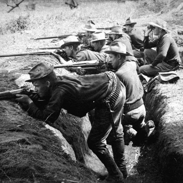 During the Philippine-American War, members of an unidentified American Army regiment shoot at Filipino insurgents while positioned in trenches, 1899. (Photo by Interim Archives/Getty Images)