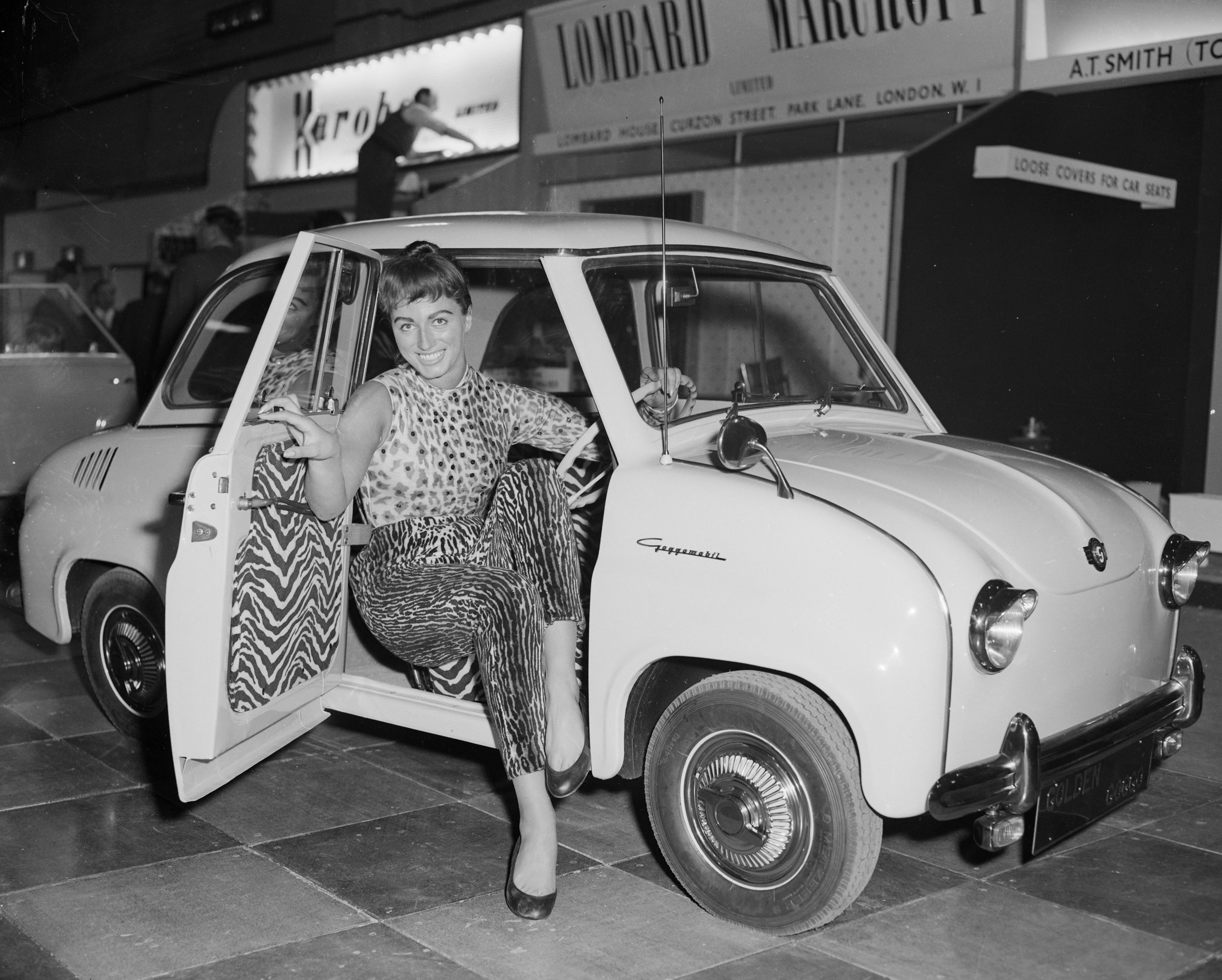 16th October 1956:  Model Jackie Collins at the Motor Show, Earl's Court, London, wearing a leopard print outfit designed by Car Robes, makers of car seat covers. She is sitting in a Goggomobil T300, the smallest family four-seater car on the market, which is made in Bavaria.  (Photo by Ron Burton/Keystone/Getty Images)