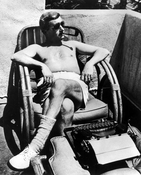 American author William Faulkner (1897 - 1962) reclines in a chair in front of typewriter and smokes a pipe, Hollywood, California, early 1940's. He is shirtless, and wears sunglasses, shorts, and wool socks. (Photo by Alfred Eriss/Pix Inc./The LIFE Picture Collection/Getty Images)