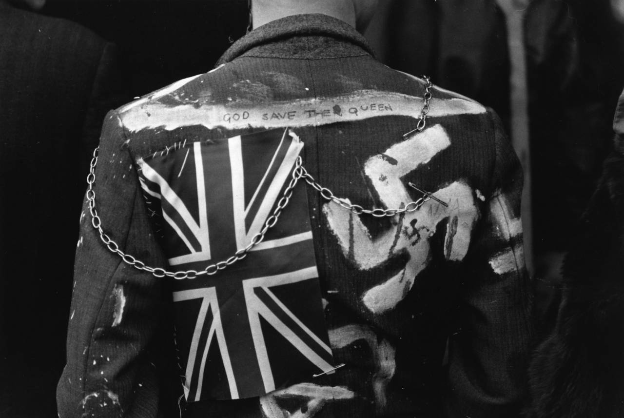 The back of a leather clad Punk Rocker with 'God Save The Queen', a swastika and a Union Jack decorating the jacket.    (Photo by Chris Moorhouse/Getty Images)