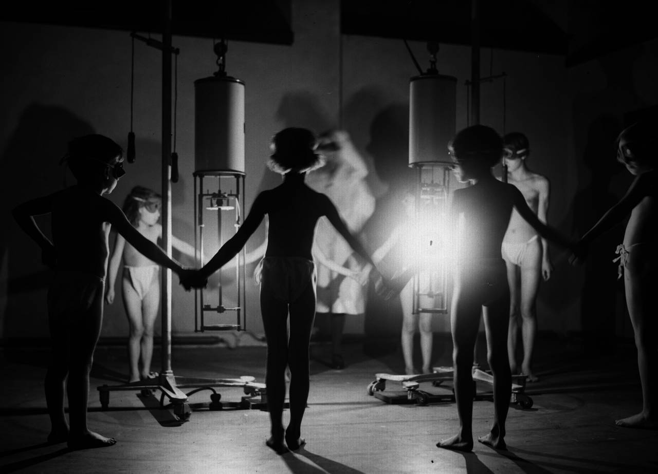 A group of children hold hands around a radiating glow of ultraviolet light at the Institute of Ray Therapy.   (Photo by Fox Photos/Getty Images)