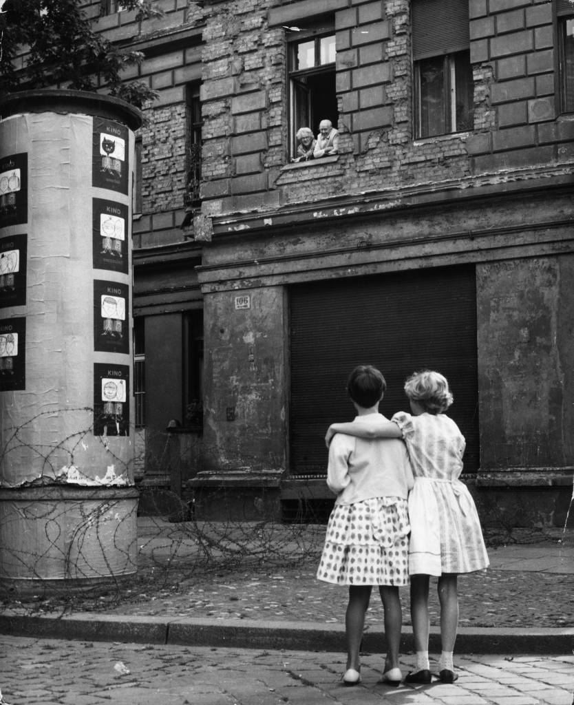 14th August 1961: Two little girls in a  West German street chat with their grandparents in the window of their home in the eastern zone, separated only by a barbed wire barricade.  (Photo by Keystone/Getty Images)