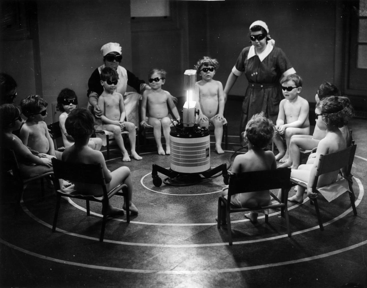 January 1938:  Three nurses and a group of young children sitting around a Centrosol sunray lamp at the Miriam Price Coleman day nursery.  (Photo by Fox Photos/Getty Images)