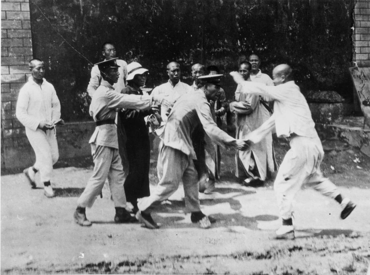 September 1923:  Chinese eunuchs scuffle with police following their eviction from the Forbidden City in Beijing by order of the Emperor.  (Photo by Topical Press Agency/Getty Images)