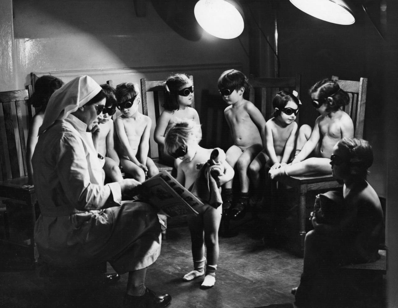2nd March 1942:  A nurse watching over children in Bermondsey, London, sitting under sun-ray lamps to help make up the deficiency in sunlight and the lack of certain items of food, such as fruit, during the winter months of the Second World War.  (Photo by Fox Photos/Getty Images)