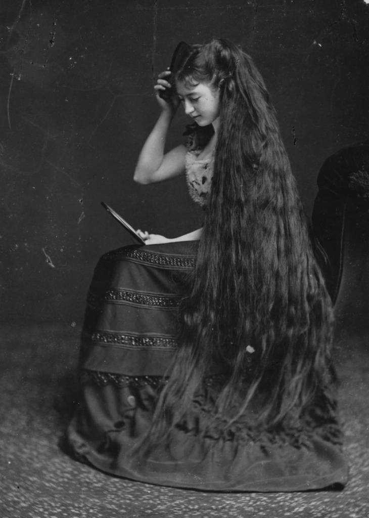 circa 1885:  Mrs Frampton combing her long hair with the help of a mirror.  (Photo by London Stereoscopic Company/Getty Images)