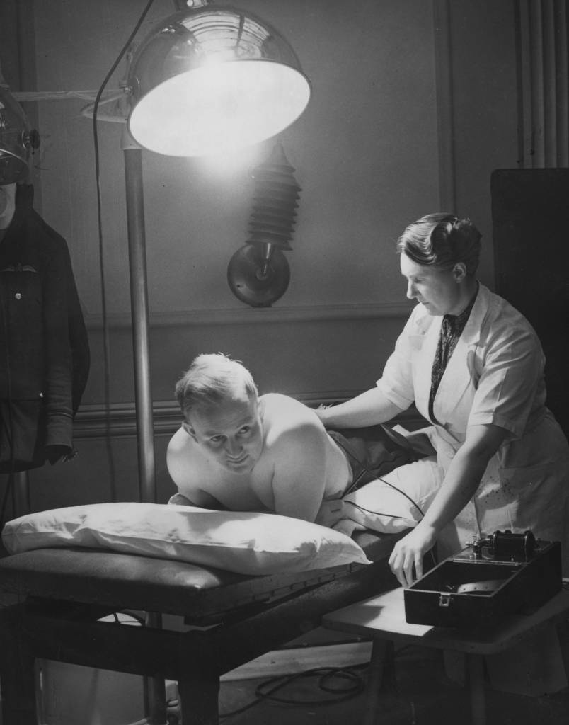 24th May 1941:  An RAF Flying Officer receiving Sun-Ray and electrical treatment after suffering a broken back.  (Photo by P. R. Poukev/Fox Photos/Getty Images)